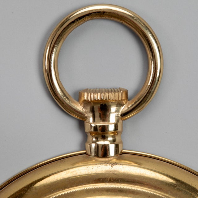 French brass framed wall mirror imparts a sense of whimsy with its pocket watch shape, circa 1950s. Diameter of actual...