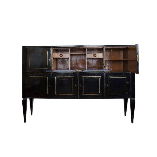 Italian Ebonized Bronze-Inlaid Cabinet On Tapered Legs. This cabinet features seven doors and a cherrywood interiors.
