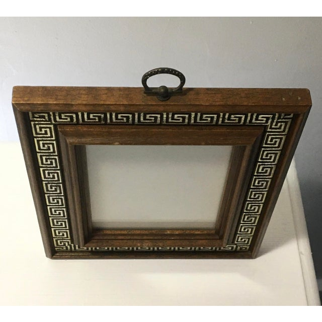 Bold but small brass ring carved wood frame with glass front. Dark wood frame consisted of several levels of dark wood w/...