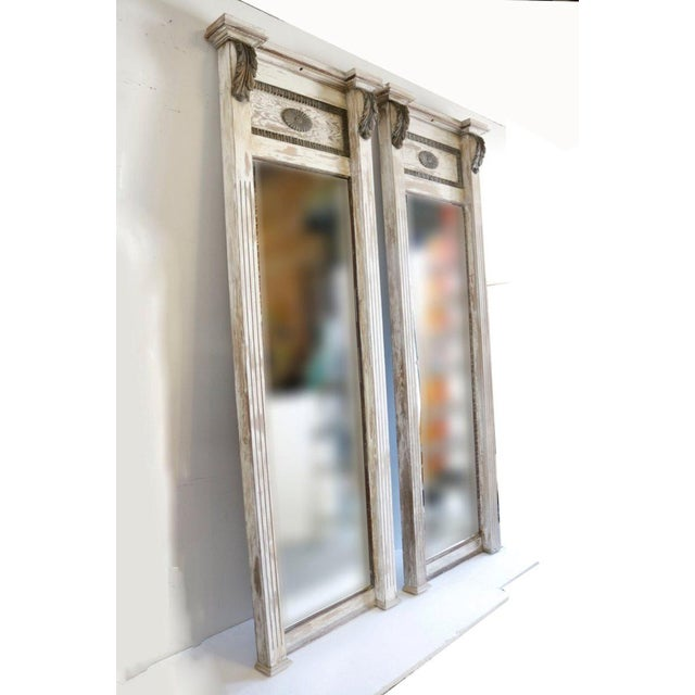 A pair of full-length 19th century mirrors with a crown molding and acanthus details. The weathered wood shows their full...