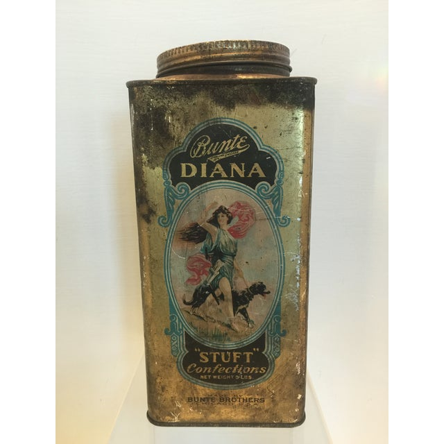 Great vintage candy tin from the 1920's with beautiful graphics. The natural patina due to its age just adds to the charm....