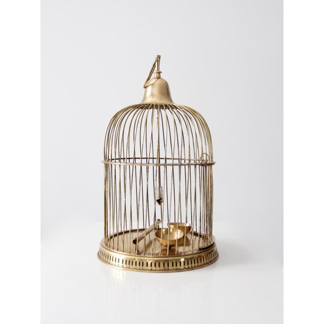 This is a vintage brass bird cage. The decorative bird cage features slender bars with a round base with perforated...