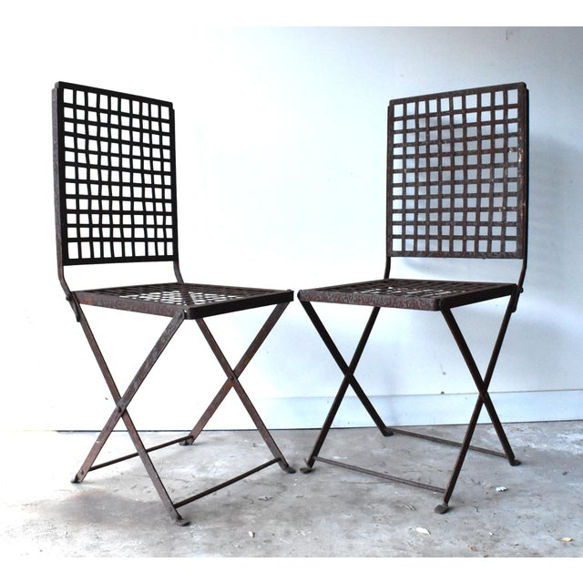 A pair of vintage, c. 1940s, wrought iron folding garden chairs with woven metal seats and backs.