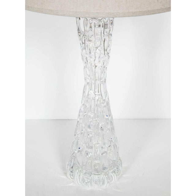 Mid-century modern handblown crystal glass lamp with highly stylized hourglass form. The lamp features faceted ice glass...