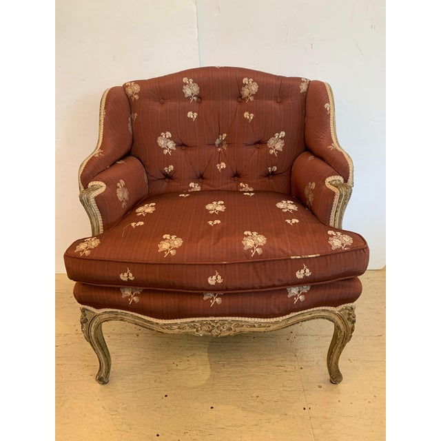 A romantic French Louis XV armchair, generous in width but still feminine in stature having a worn creamy painted finish...
