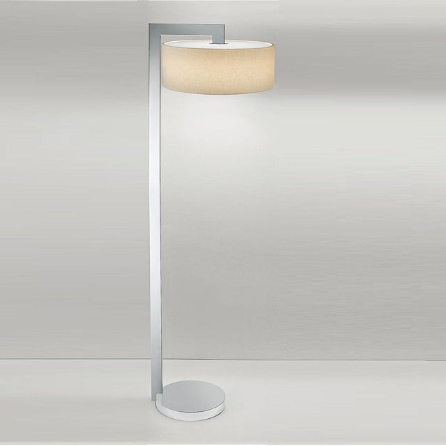 Art deco style lamp in polished chrome. A circular base with a stepped detail. Linen shallow shade with an integral LED...