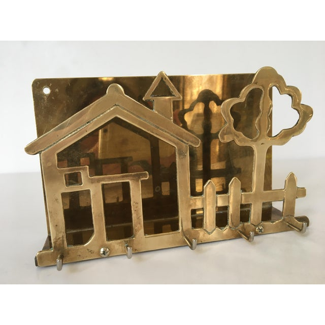 Offering a mid century brass letter holder and key/leash rack with five hooks. This brass piece can sit on a desk or be...