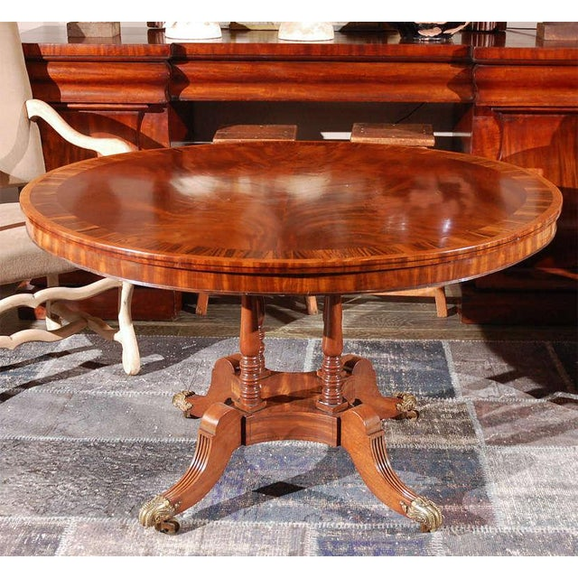 1840s English round mahogany breakfast table with a rosewood banded top on a four-turned column pedestal base with reeded...