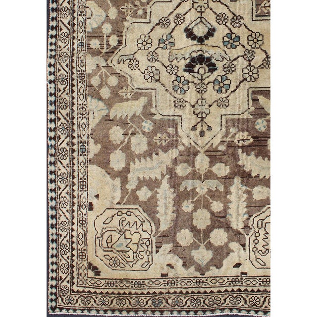 This Semi Antique rug features a center medallion design in a neutral color palette with brown outlines. The piece is from...