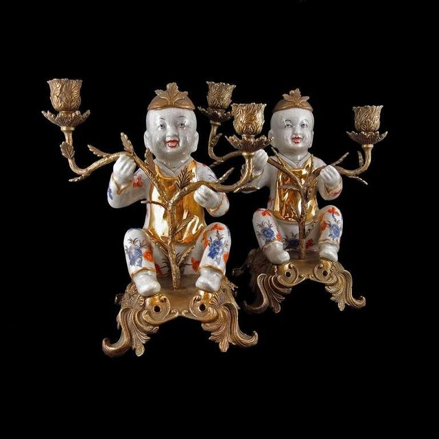 A delightful pair of two arm candelabra, each featuring a porcelain figure of a laughing boy set in ormolu mounts. The...