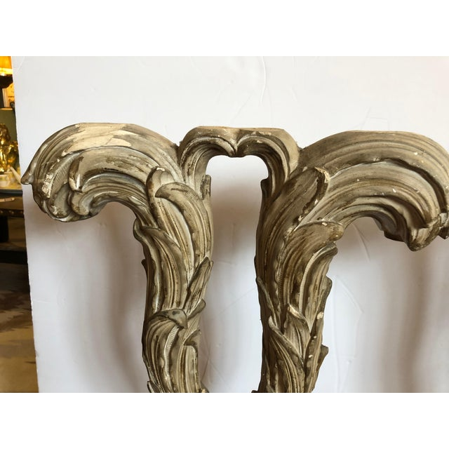 Two carved wood elongated tall architectural fragments that we call feather sculptures, mounted on faux painted green...