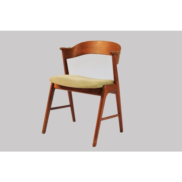 Set of eight dining chairs in teak with curved backrests and elegant frames. The chairs are commonly known as model 32 and...