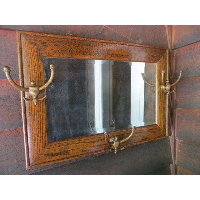 A handsome antique tiger oak wall mirror with three hooks. The wood frame is in great condition for its age. The mirror...