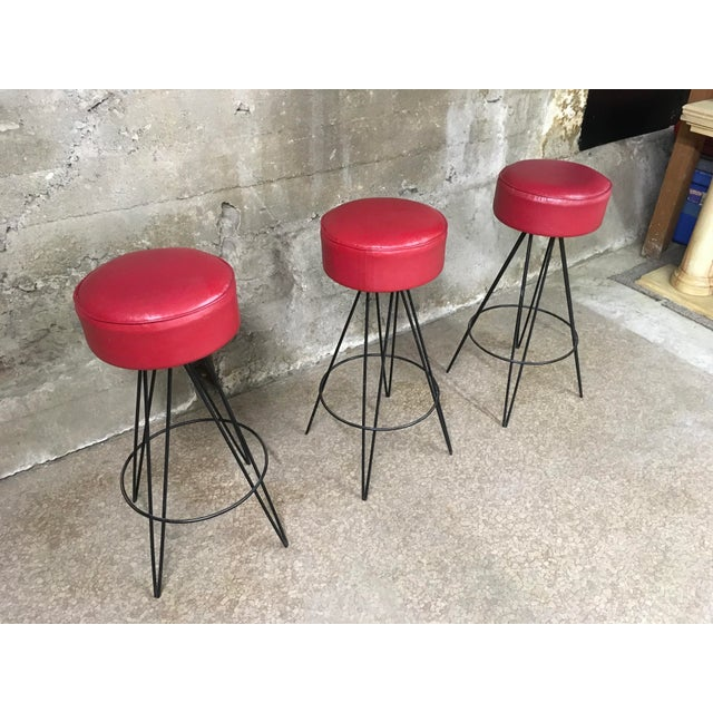 Great set of three Mid Century iron base barstools it's vibrant red vinyl tops. Bases are nice black iron and in the...