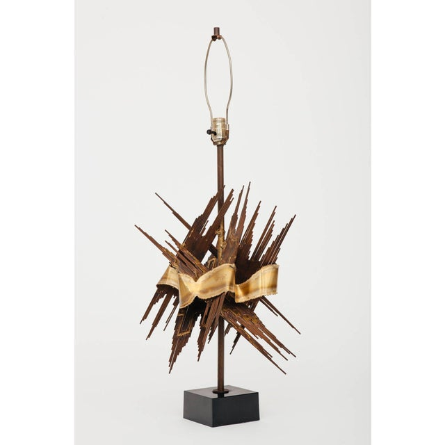 Brutalist style 1970s lamp attributed to Tom Greene crafted of torch cut metal on black square metal base. Lamp height...