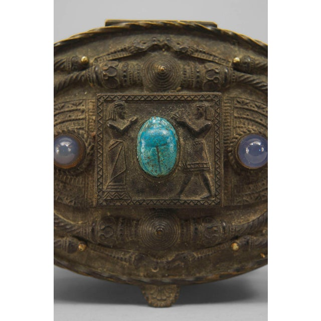 Egyptian Revival Style box of probable late 19th century French origin. The oval box is cast from dark bronze and...