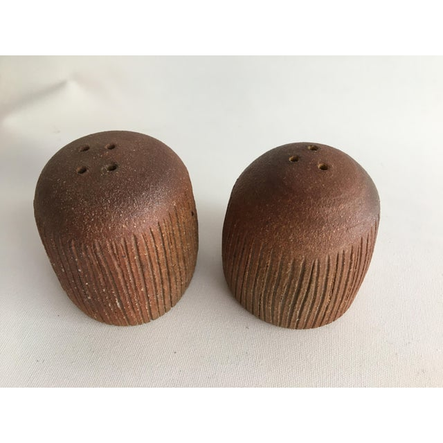 These ceramic shakers are super cute and feature hand etching. Most likely a studio piece. Includes a little cork pop at...