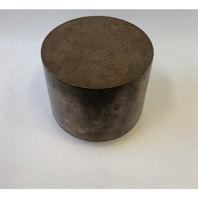 A drum side table from the 1980's by Steve Chase. The table is constructed of wood with a texture aged bronze finish and a...