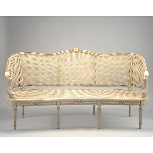 Circa 1900 French settee has eight legs and a caned seat and back rest. Three carved floral embellishments which also...