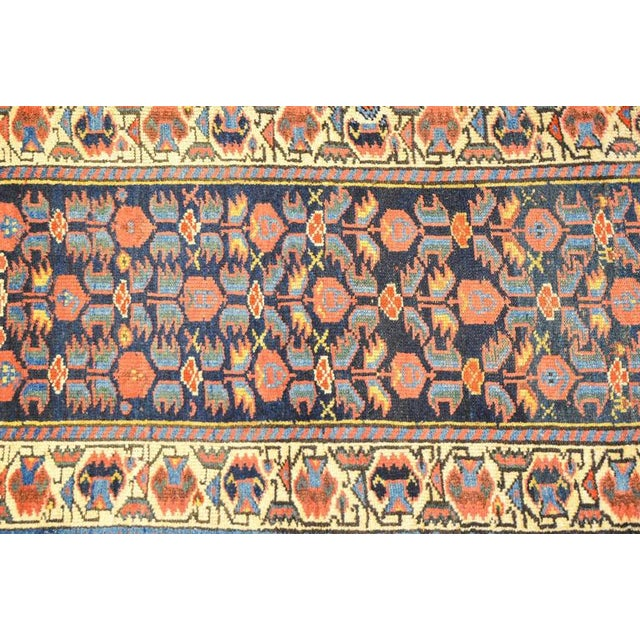 A wonderful early 20th century Persian Kurdish runner with a sweet all-over crimson and indigo floral pattern on a dark...