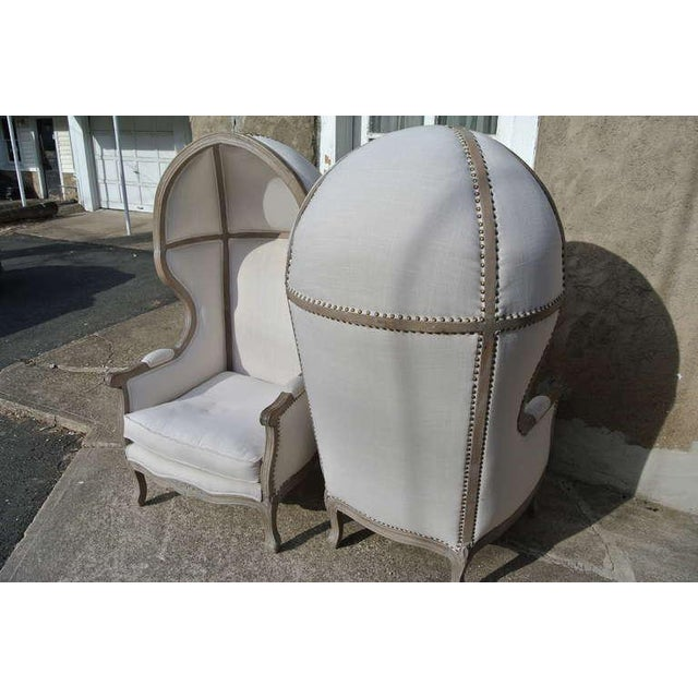Beautiful pair of Rustic French canopy hood bishop's chairs. Faded wood frame with newly reupholstered in white linen with...