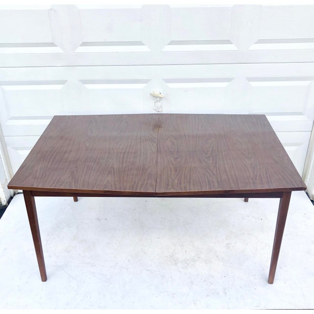 This vintage modern dining table features walnut finish legs and faux wood style formica stop, making a durable multi-use...