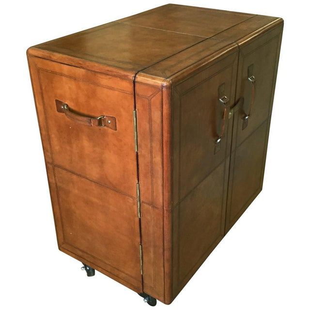 Like the stalwart trunks that accompanied travelers by sea and rail a century ago, this leather bar cabinet is built of...
