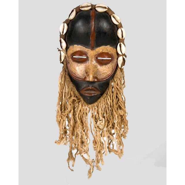 Dan Mask from the tribal people of Liberia. Tribal mask is painted gold, black and red with cowrie shells and rope. The...