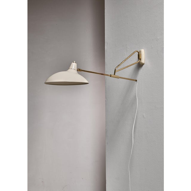 A model 6777 wall lamp by Kaiser, Germany. The lamp has a brass, swiveling and adjustable stem and a white lacquered metal...