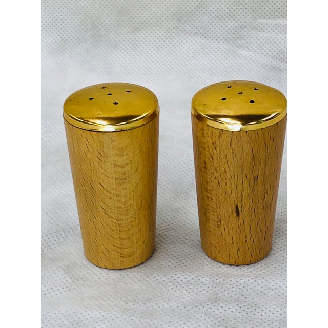 Mid Century Wooden salt and pepper shakers are embossed in gold with letters S and P.