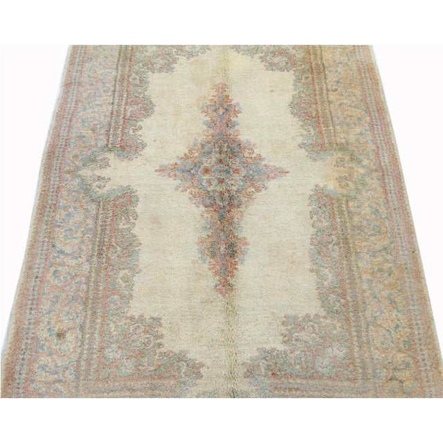 Old handwoven Kerman rug featuring a floral medallion on an ivory colored field and light blue border accented in shades...