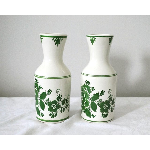 A pair of vintage Delft Green carafes or liquor bottles, dating to the 1970s or so. The ceramic bottles are off white and...