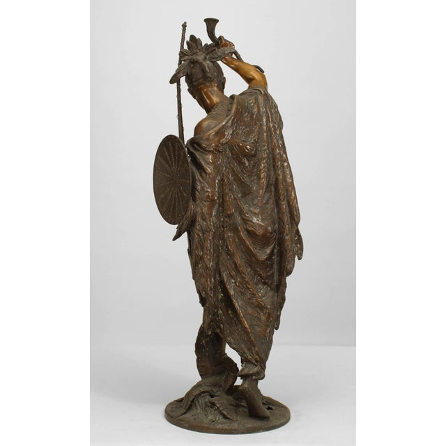 American lacquered metal figure of Indian warrior with shield & bow holding horn on a naturalistically cast circular base...