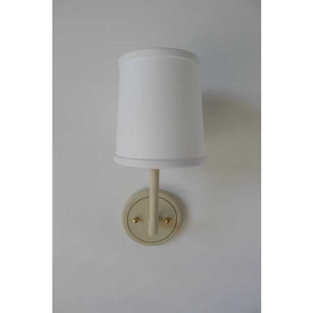 Paul Marra Leather Wrapped Adnet inspired wall sconce, shown in cream, with top-stitched detailing. Top-stitching detail...
