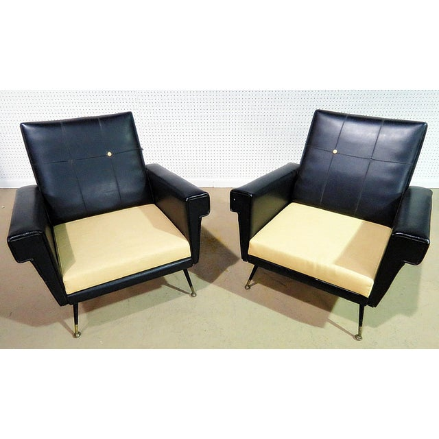 Pair of vintage Italian vinyl and fabric upholstered arm chairs with metal legs and brass sabots.