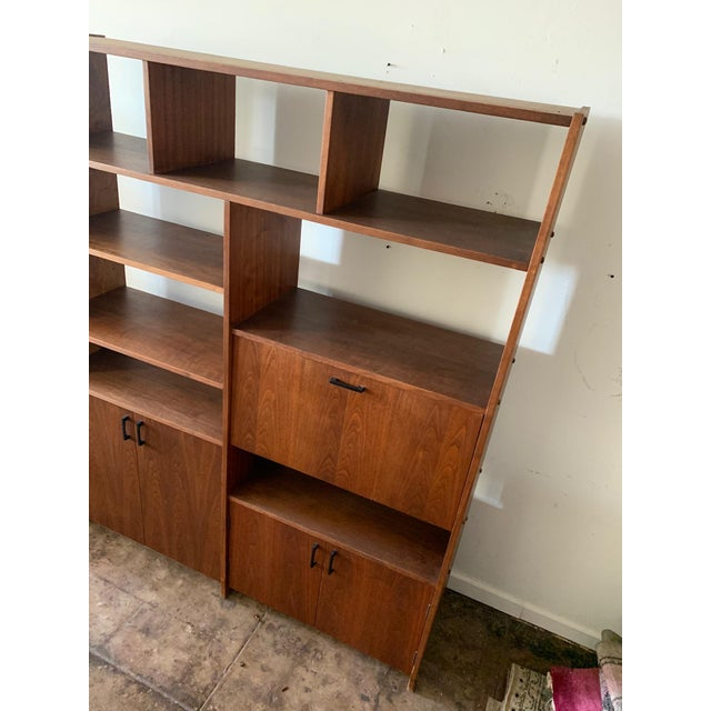 Mid-Century walnut shelving unit with cabinets and pull down desk. Beautiful and original condition, matte stain shows off...