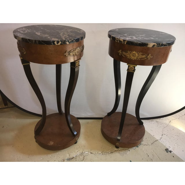 Offered is a pair of Empire style marble top pedestals. Each with bronze mounts. Ebony and burl wood decorated sitting on...