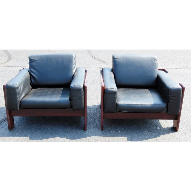 Pair of Mid Century Modern club chairs with vinyl upholstery.