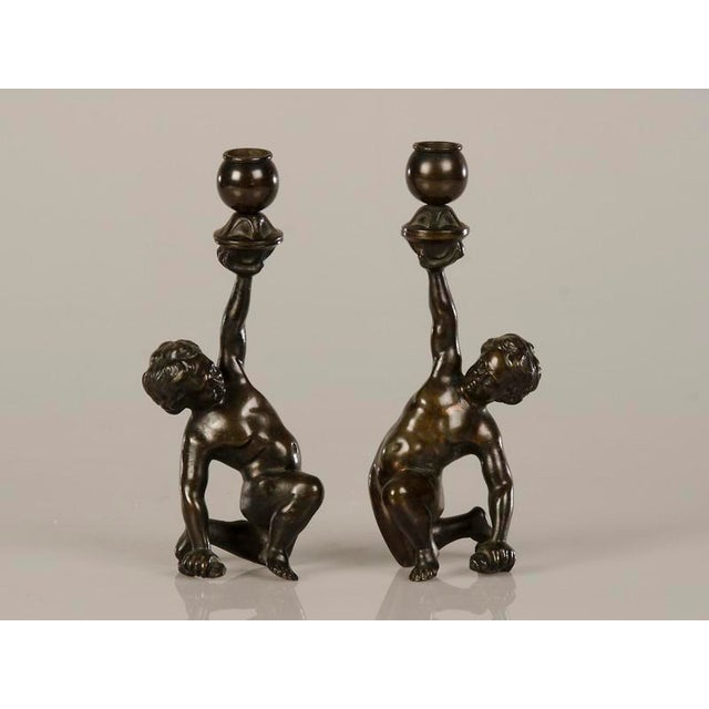 A pair of cast bronze candlesticks each featuring a kneeling putto from Italy c.1880. These charming candlesticks have a...