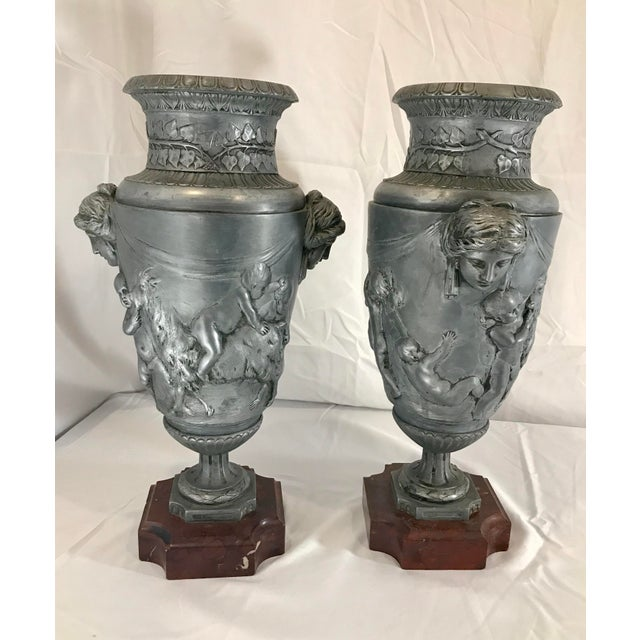 A pair of French Neoclassical ornamental highly detailed metal/pewter urns featuring putti playing, riding and carrying...
