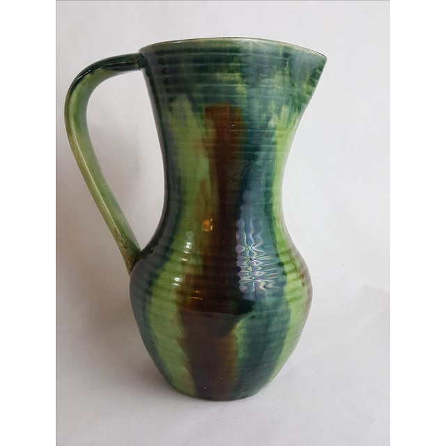 Gorgeous multicolor drip technique glaze. Simple lines on the pitcher allowing the glaze to shine. Small repair on lip of...