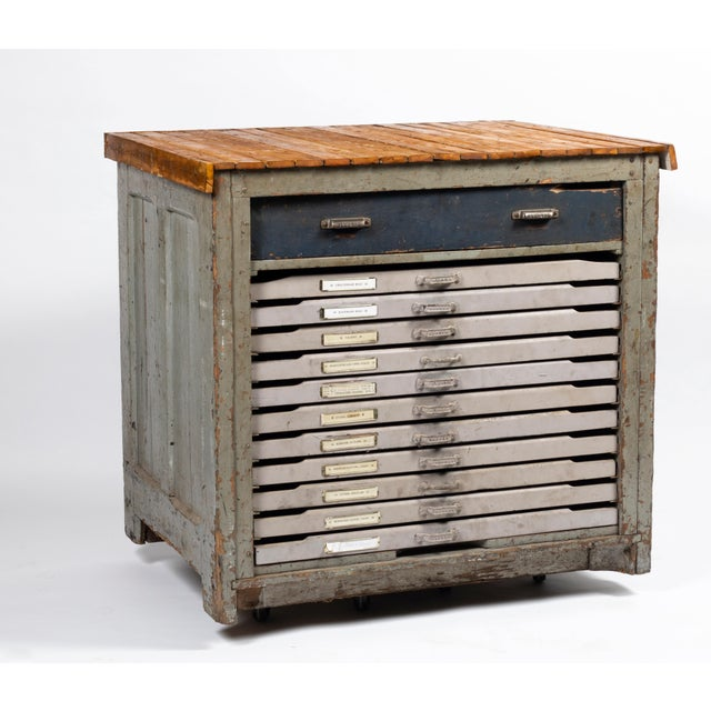 This antique printmaking cabinet features all wooden construction with flat file drawers. Each of the drawers has separate...