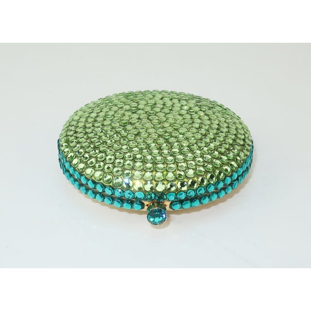 A collectible powder compact by Estee Lauder resembling a yummy macaroon in a vibrant spring green and aqua blue pave...