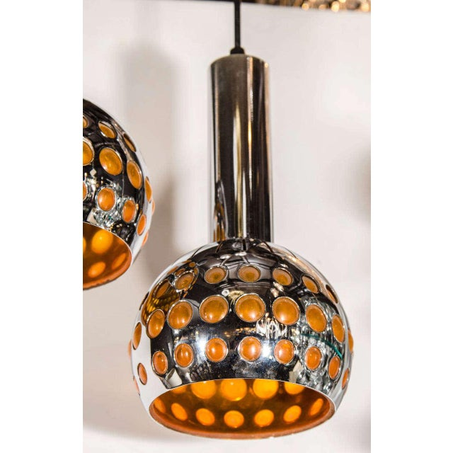 Pair of mid century modern chrome pendant lights with sculpted globe forms and with geometric perforated design. The...