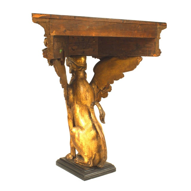 French Empire gilt sphinx carved triangular console table with black painted top.