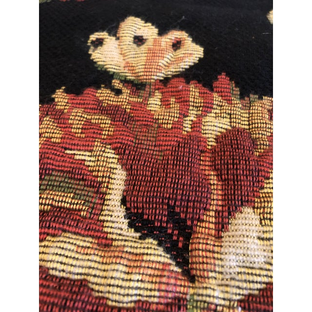 A striking French tapestry having black background and gorgeous rich floral in gold, blue, pink and green. There's a rod...