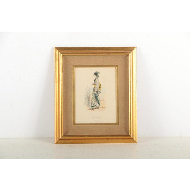 A vintage pair of 19th century hand colored French intaglio prints on paper of Japanese costumes. Featured is a depiction...