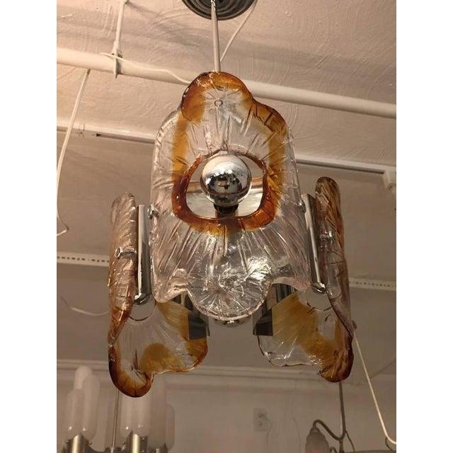 Stunning Italian Mid-Century Modern Murano chandelier by Mazzega having three clear and amber handblown glass shades on a...