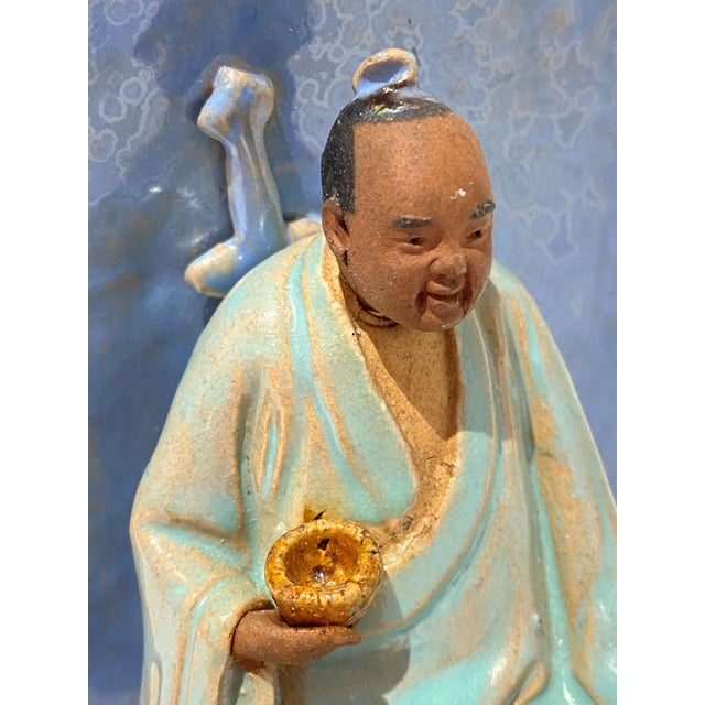 Unusual early 20 Century pottery figurine of the Buddha with Alms Bowl and carrying the sword of his early martial youth...