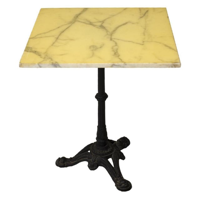 French stone top bistro table with cast iron pedestal base, 20th C. The Carrara marble stone top is covered with yellowed...